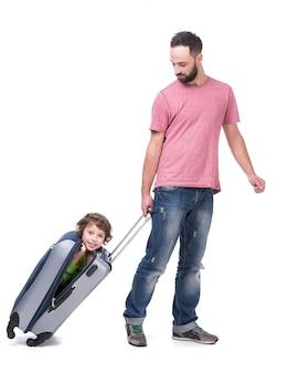 Papai colocou o filho em uma mala e o carrega.