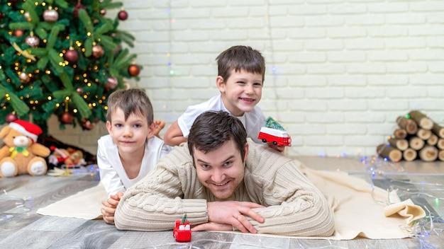 Papai com seus filhos estão brincando no chão perto da árvore de natal em casa. ideia de família feliz