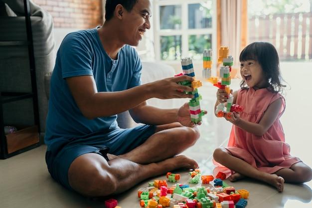 Papai e criança brincando com tijolos de plástico