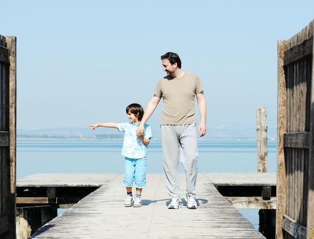 Papai e criança pela doca em um belo mar
