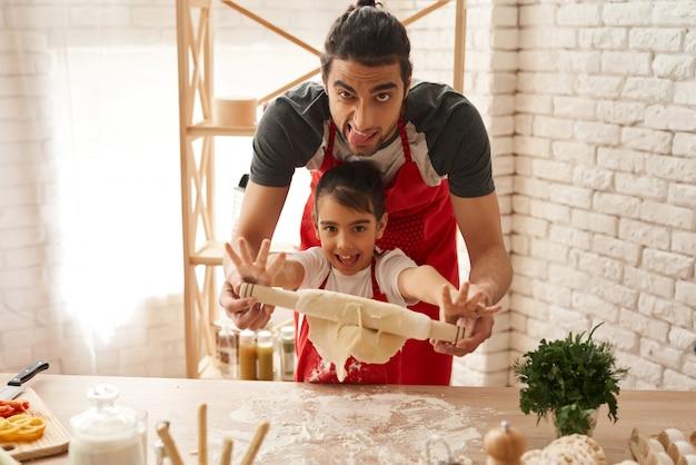 Papai e daighter estão atacando com massa na cozinha.