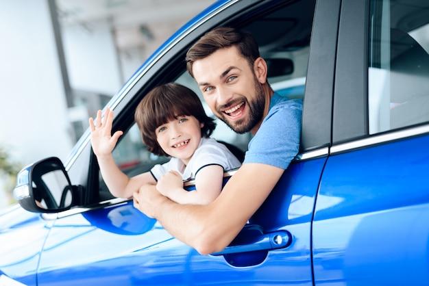 Papai e filho olham para fora da janela do carro e sorriem.