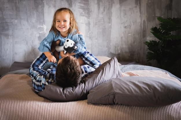 Papai e sua filha brincam na cama no quarto, sorrindo e rindo