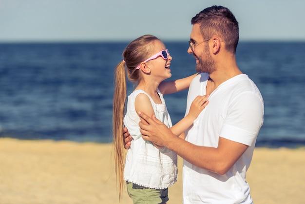Papai e sua filha em óculos de sol estão sorrindo.