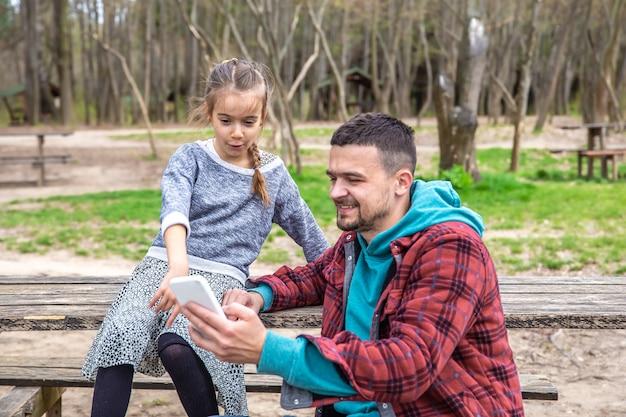 Papai e sua filha olham para o telefone enquanto caminham na floresta.