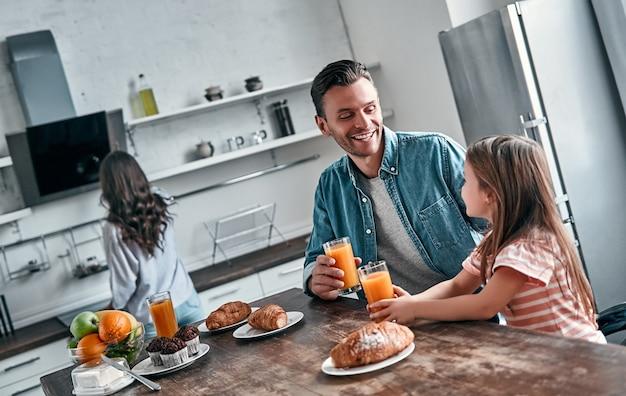 Papai e sua linda filha tomam café da manhã na cozinha e conversam. mamãe se prepara para comer no fundo. conceito de família feliz.