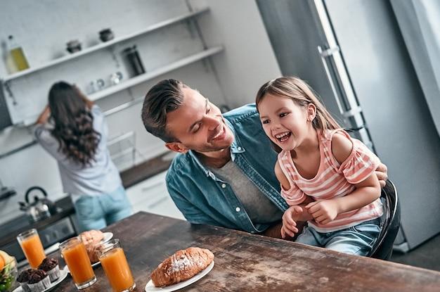 Papai e sua linda filha tomam café da manhã na cozinha e riem. mamãe se prepara para comer no fundo. conceito de família feliz.