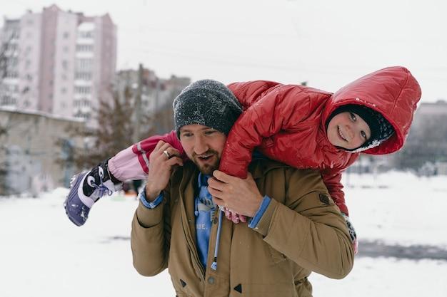 Papai está segurando uma filha nos ombros.