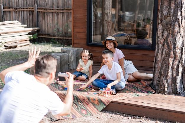 Papai fotografa sua esposa e dois filhos em uma câmera de filme, e a família se diverte nas férias de verão. sentado em um tapete bordado na varanda perto de uma casa de madeira.