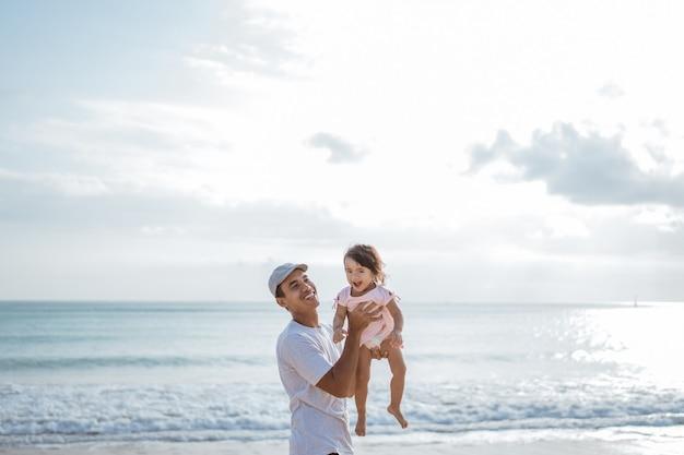 Papai gosta de brincar com a filha na praia se divertindo juntos