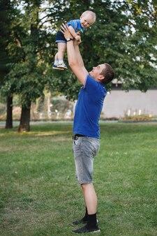 Papai joga seu filho nos braços estendidos