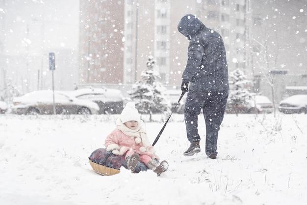 Papai leva a filha pequena em um tubo durante uma forte tempestade de neve