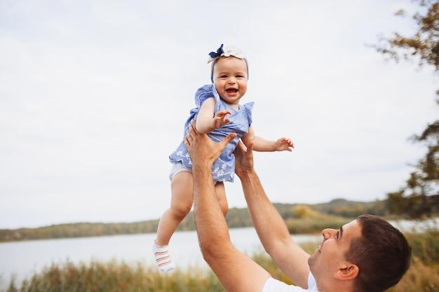 Papai levanta as mãos com uma menina em pé diante do lago