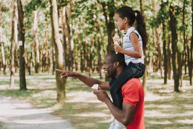 Papai mostra o caminho para a garota que está sentada em seu pescoço.