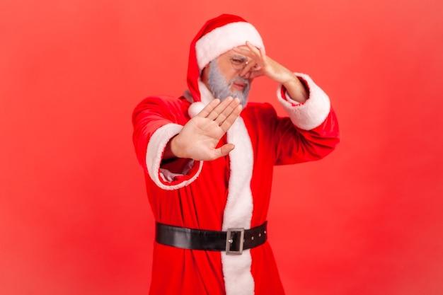 Papai noel apertando o nariz com os dedos para evitar o mau cheiro e mostrando um gesto de parar