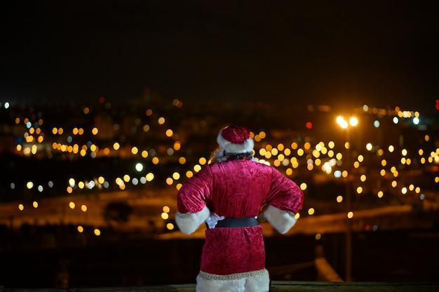 Papai noel assistindo a cidade à noite
