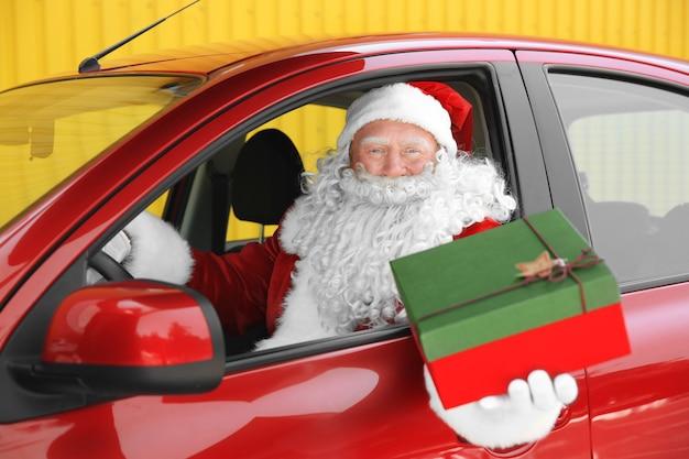 Papai noel autêntico com caixa de presente em carro vermelho