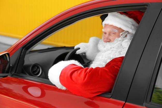 Papai noel autêntico dirigindo seu carro vermelho, ao ar livre