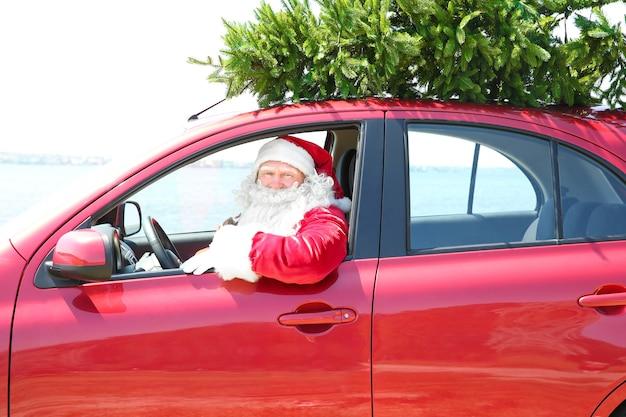 Papai noel autêntico dirigindo um carro com uma árvore de natal no topo