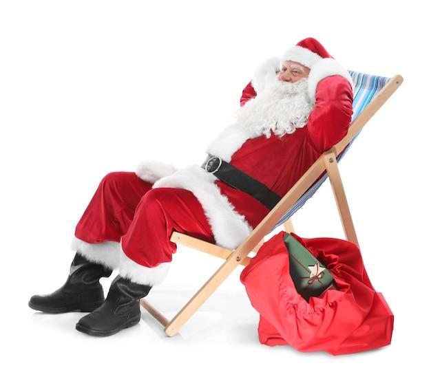 Papai noel autêntico sentado em uma cadeira de praia contra um fundo branco