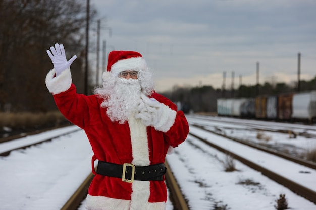 Papai noel caminhando na estrada rai e acenando com a mão no dia de natal carregando uma sacola de presentes