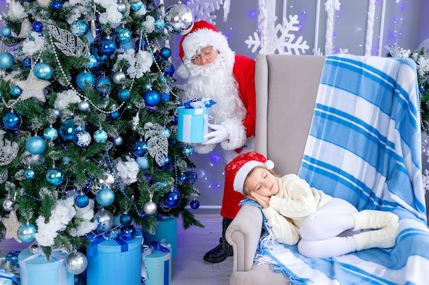 Papai noel coloca um presente debaixo da árvore enquanto a criança está dormindo