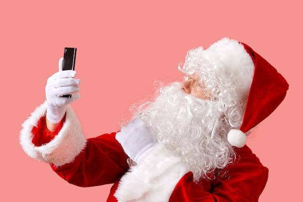 Papai noel com celular isolado em fundo rosa