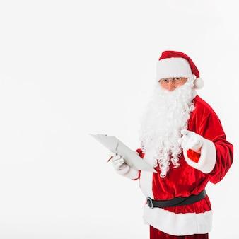 Papai Noel com dedo apontando da prancheta na câmera