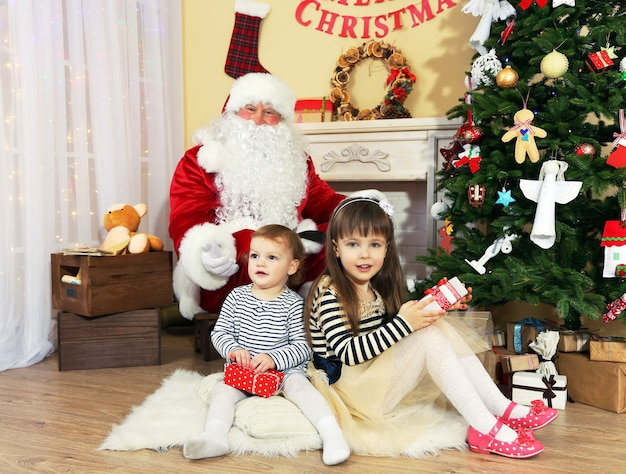 Papai noel com duas garotinhas fofas perto da lareira e a árvore de natal em casa