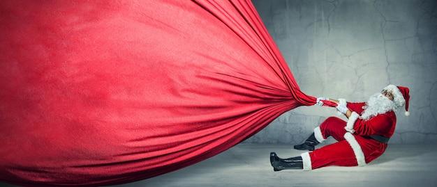 Papai noel com saco grande no banner de propaganda em branco, com espaço de cópia. tema de natal, vendas - imagem stock