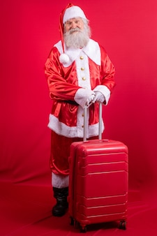 Papai noel com sua mala. conceito de viagens de ano novo. papai noel no aeroporto.