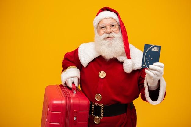 Papai noel com sua mala. segurando um passaporte brasileiro. conceito de viagem de ano novo