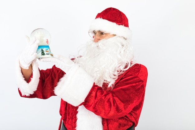 Papai noel com um globo de neve de natal nas mãos, em fundo branco