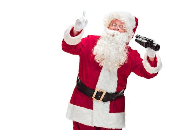 Papai noel com uma barba branca luxuosa, chapéu de papai noel e um traje vermelho isolado em um fundo branco com binóculos