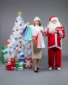 Papai noel com uma jovem em volta dos presentes de natal em fundo cinza.