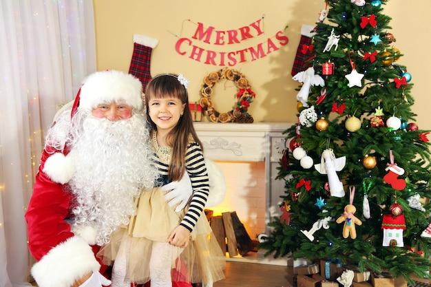 Papai noel com uma linda garotinha perto da árvore de natal em casa
