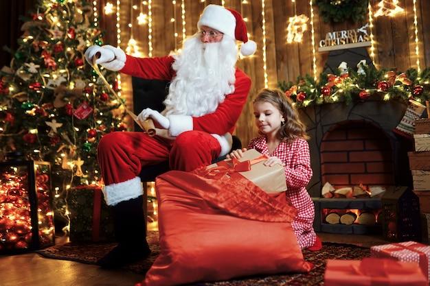 Papai noel com uma linda menina espantada em pijama embalar presentes