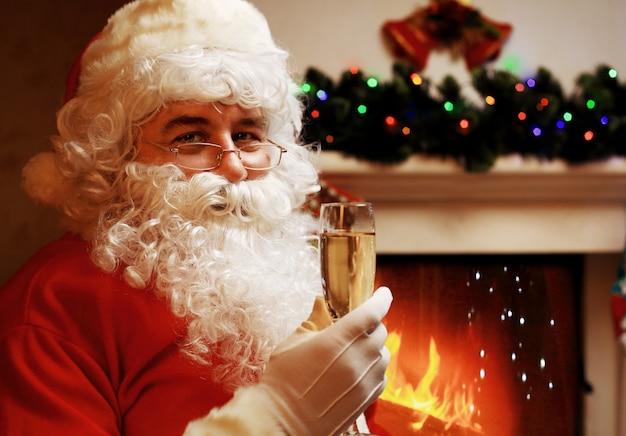 Papai noel com uma taça de champanhe espumante perto de uma árvore de natal