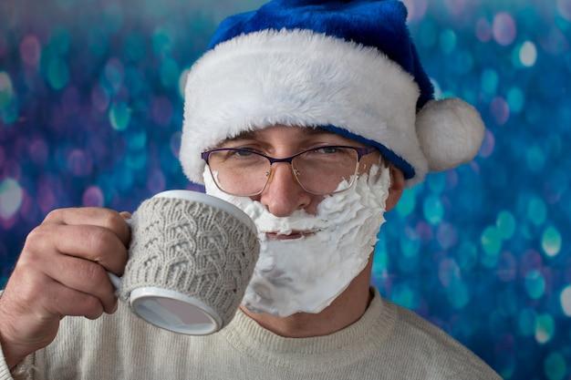 Papai noel com uma xícara de café. em um fundo azul em um ano novo capuz