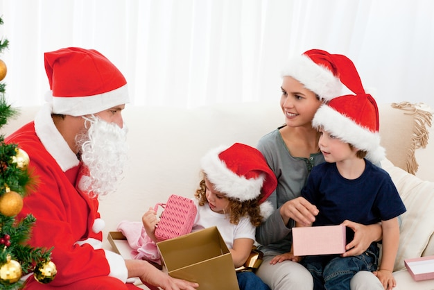 Papai noel dando presentes para seus filhos na sala de estar