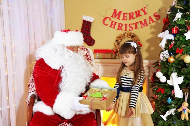Papai noel dando um presente para uma menina bonita perto da árvore de natal em casa