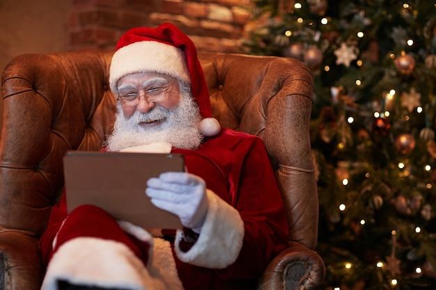 Papai noel de óculos sentado em uma poltrona de couro e compondo para estudar no tablet