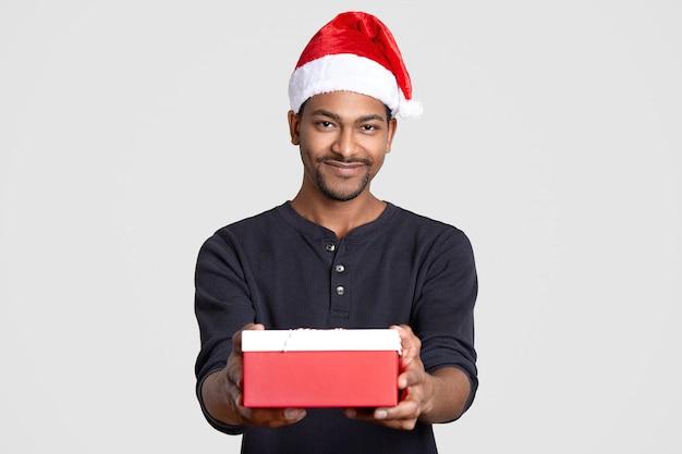 Papai noel de pele escura usa chapéu festivo, jumper casual, segura a caixa de presente, sorri alegremente, isolado sobre o branco