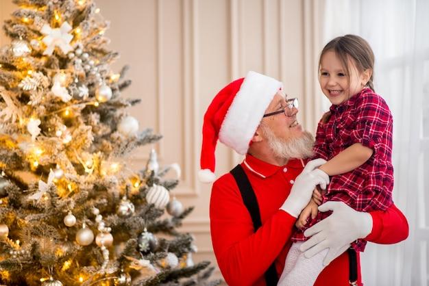 Papai noel e criança em casa contra a árvore de natal. conceito de férias em família.