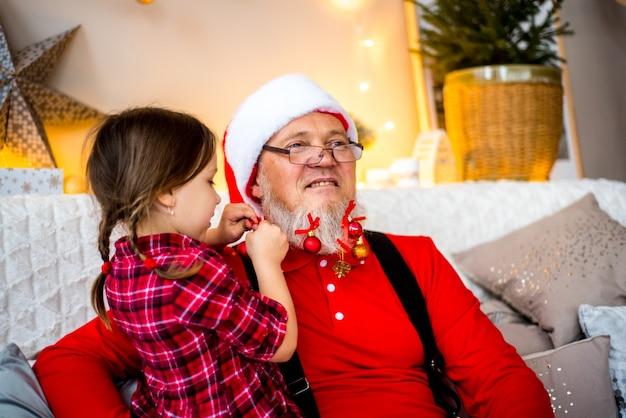 Papai noel e criança em casa contra a árvore de natal. conceito de férias em família. Foto Premium