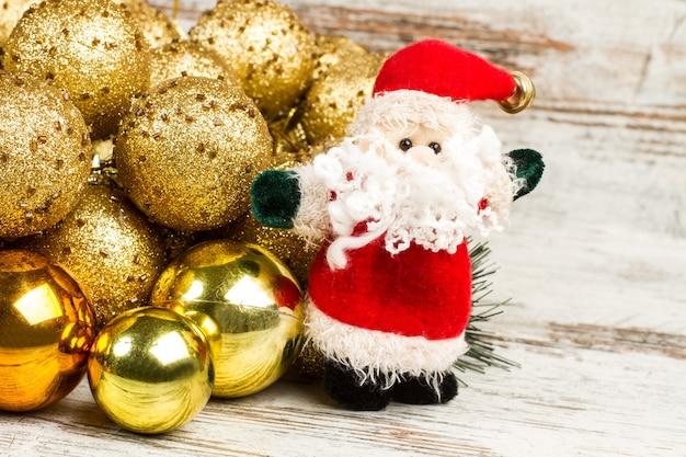 Papai noel e enfeites de natal dourados em uma mesa de madeira branca e marrom