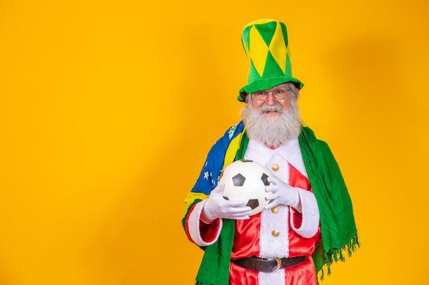 Papai noel é fã do brasil. torcedor do papai noel da seleção brasileira. campeonato esportivo. papai noel com a bandeira brasileira e uma bola. partida de futebol.