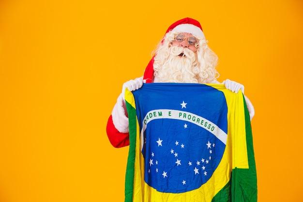 Papai noel é fã do brasil. torcedor do papai noel da seleção brasileira. campeonato esportivo. papai noel segurando a bandeira brasileira. partida de futebol.