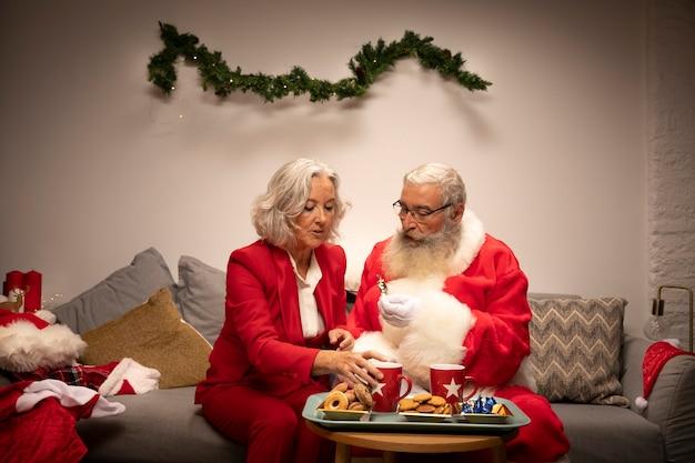 Papai noel e mulher tendo biscoitos