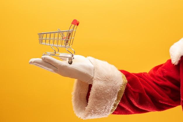Papai noel e o supermercado, ele está mostrando um mini carrinho